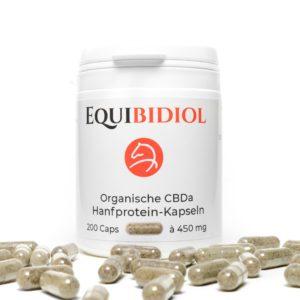 Produktfoto einer Packung Equibidol CBDa Caps mit 200 Kapseln Inhalt und davor liegenden Kapseln